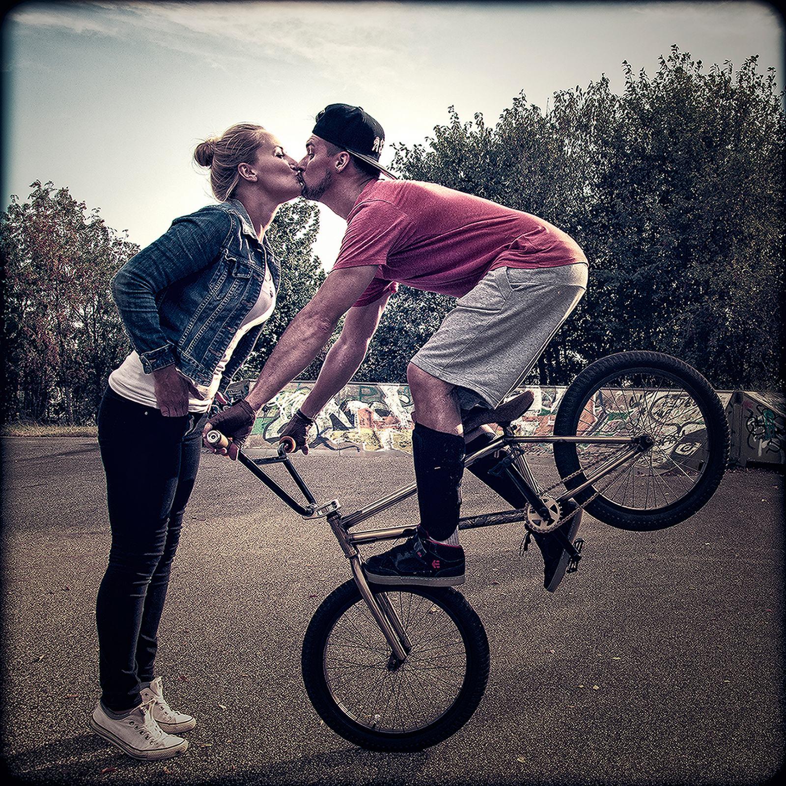Mann steht auf dem Vorderrad seines BMX und gibt einer Frau einen Kuss.