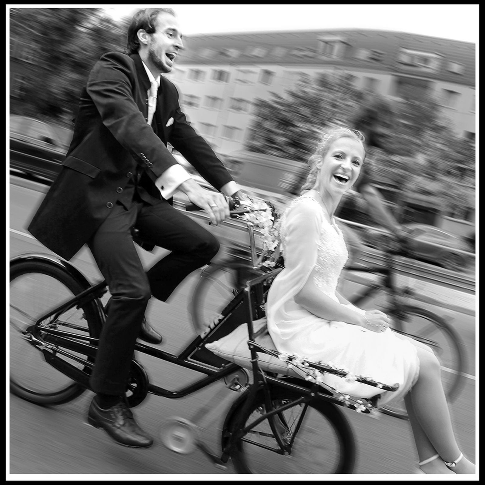 Lachende Braut wird von ihrem Bräutigam vorne auf einem Postrad sitzend gefahren.