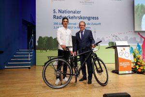 Ein junger und ein älterer Mann posieren mit schwarzem Fahrrad auf der Bühne.