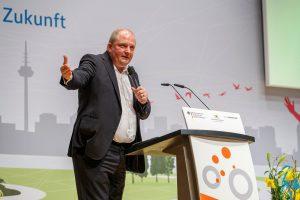 Mann steht hinter Rednerpult und hält mit einem Mikrofon in einer Hand eine Rede.