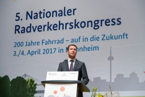 Mann in einem grauen Anzug hinter einem Rednerpult.