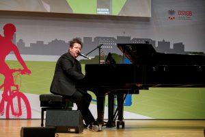Sebastian Krumbiegel sitzt auf der Bühne an einem Schwarzen Flügel und singt.