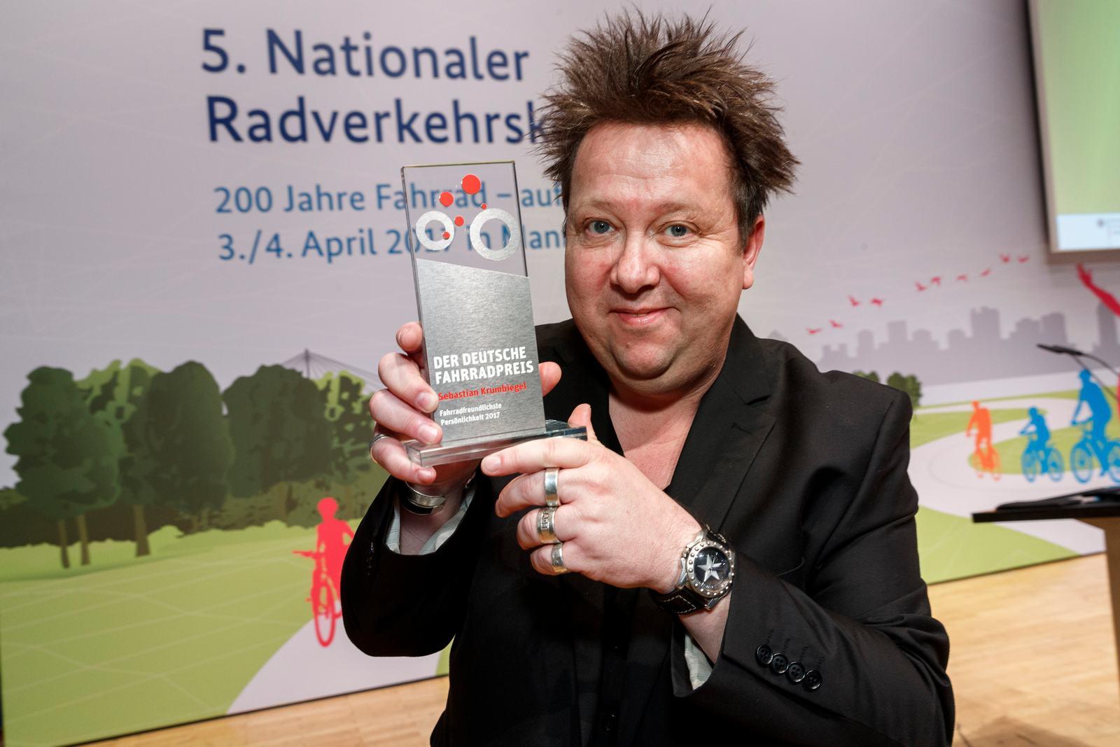 Sebastian Krumbiegel hält lächelnd seine Auszeichnung in die Kamera.