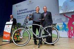 Zwei Männer posieren mit einem grauen Fahrrad mit Packmöglichkeiten auf der Bühne.