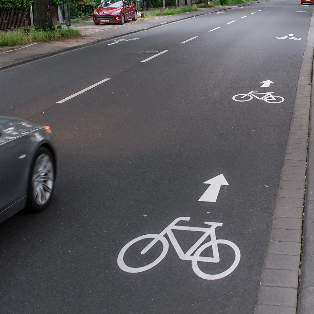 Eine asphaltierte Straße mit weißer Fahrrad und Pfeilmarkierung für den Radweg.