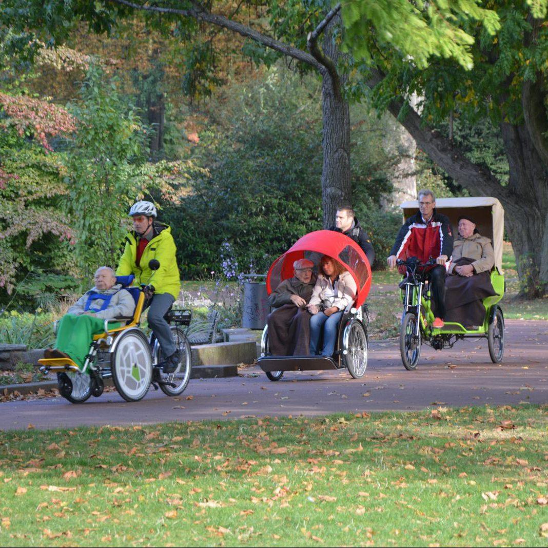 Ältere Leute die auf drei Spezialrädern durch einen Park gefahren werden.
