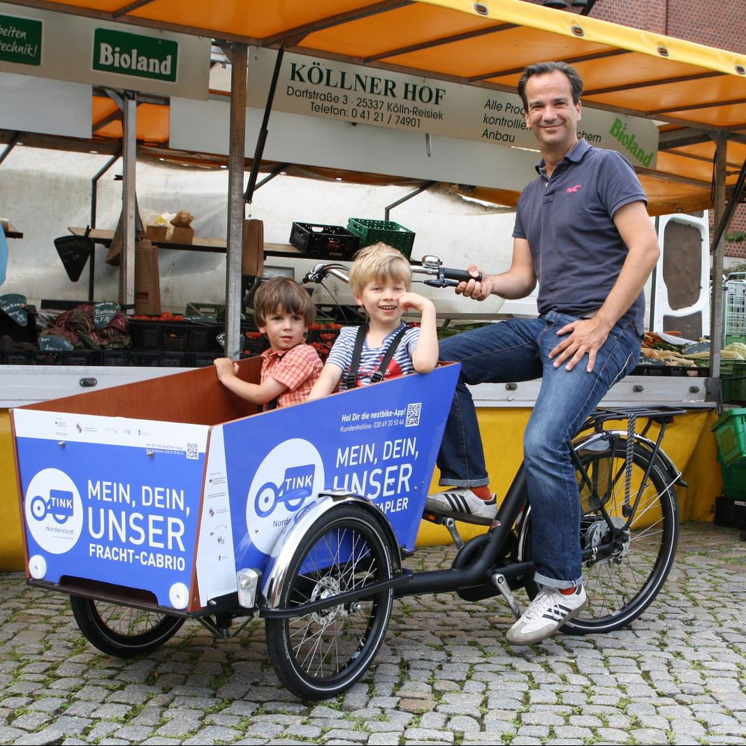 Mann sitzt auf Lastenfahrrad mit 2 jungen Kindern im Korb