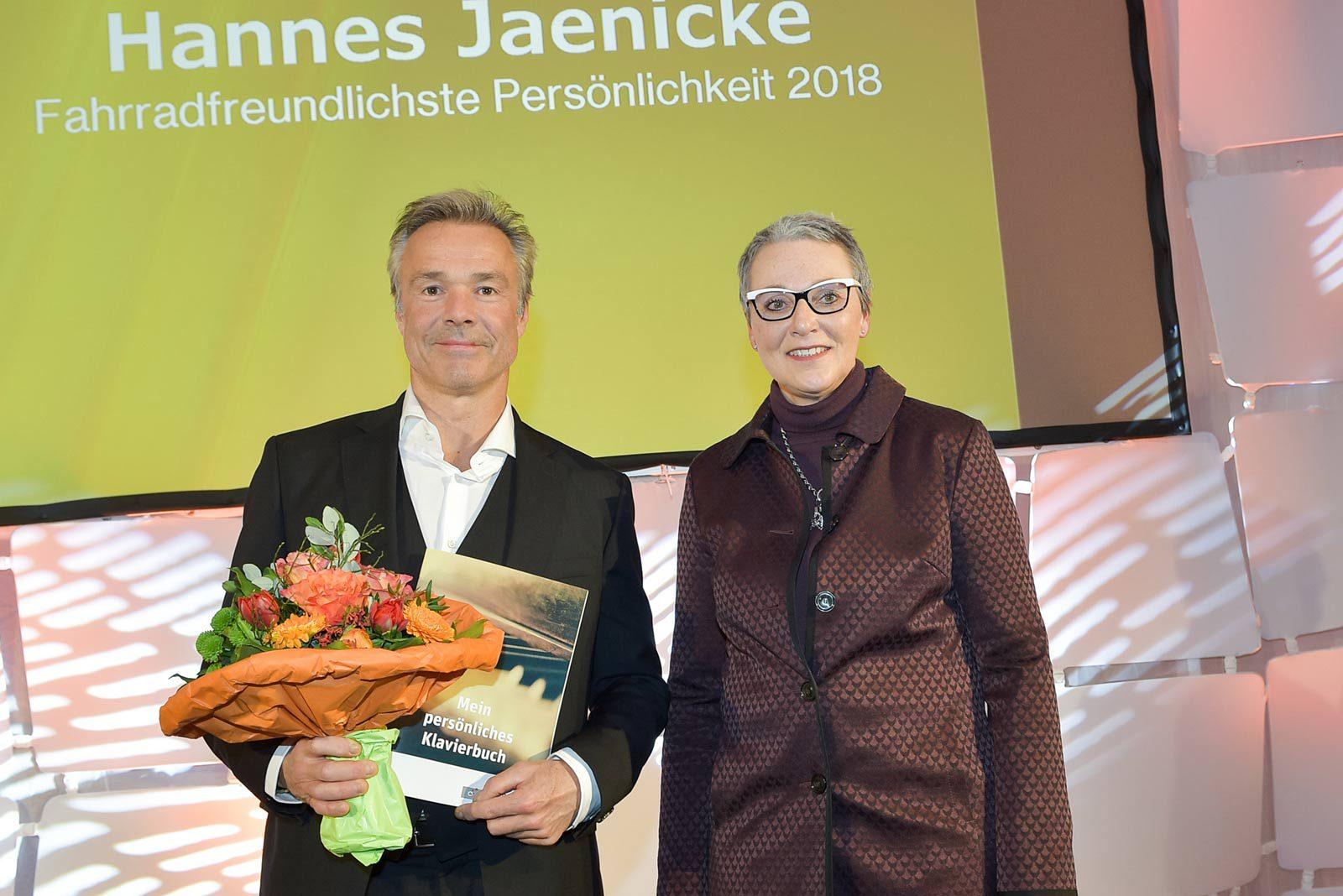 Hannes Jaenicke steht, einen Blumenstrauß haltend, neben Christine Fuchs.