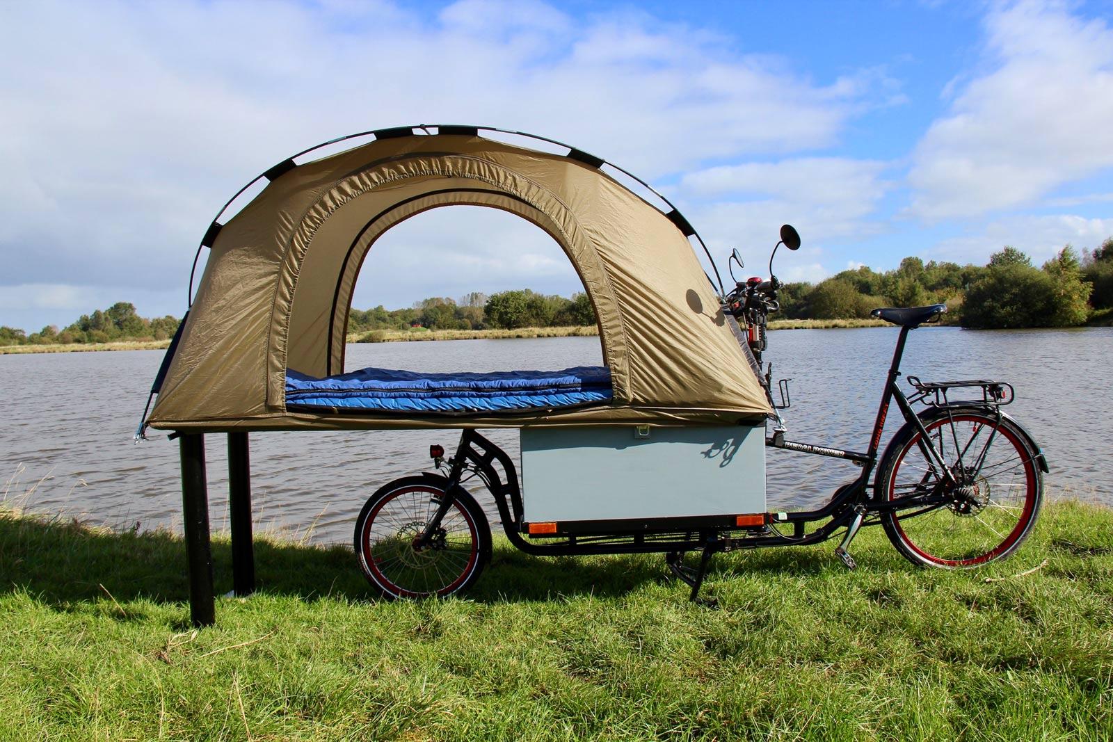 Ein aufgebautes Zelt auf einem Lastenrad im grünen, direkt vor einem Fluss.