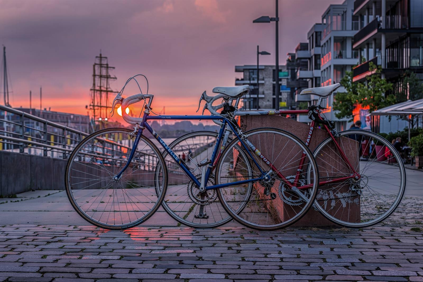 Zwei Rennräder vor einer Sonnenuntergangskulisse im Hafen.
