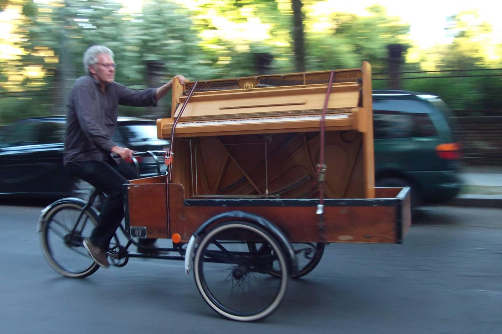 Ein Mann transportiert ein Klavier aus hellem Holz vorne auf einem Lasenrad.