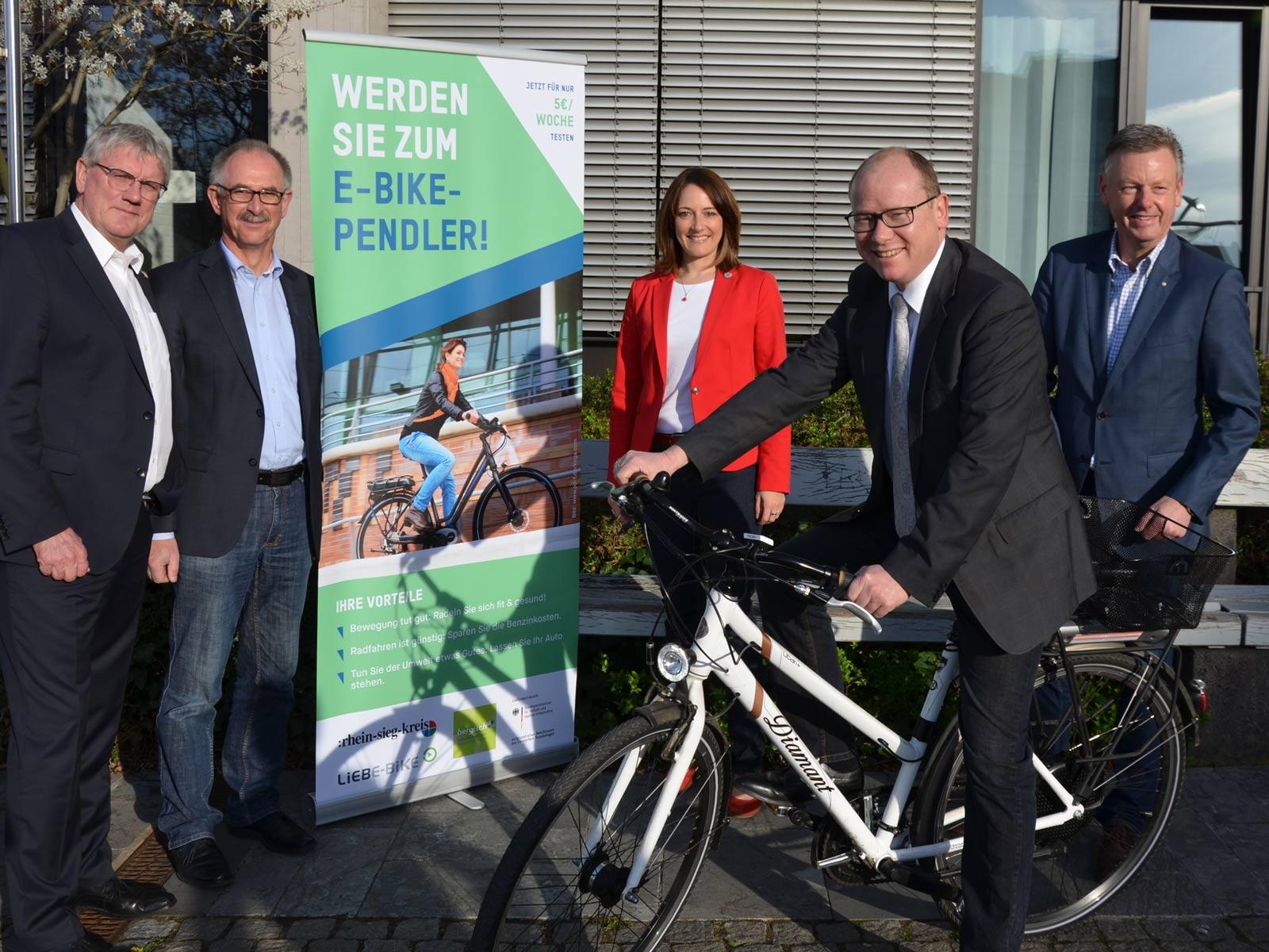 Ein Mann im Anzug sitzt auf einem Rad. Im Hintergrund stehen eine Frau und drei Männer.