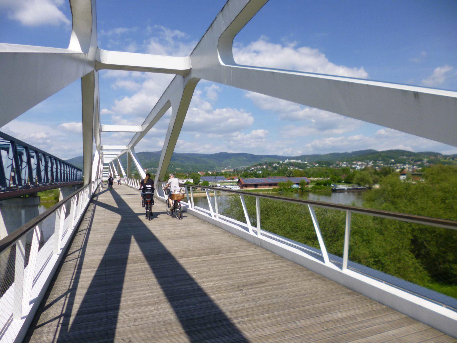 Zwei Radfahrer fahren nebeneinander auf einer Radbrücke über einen Fluss.