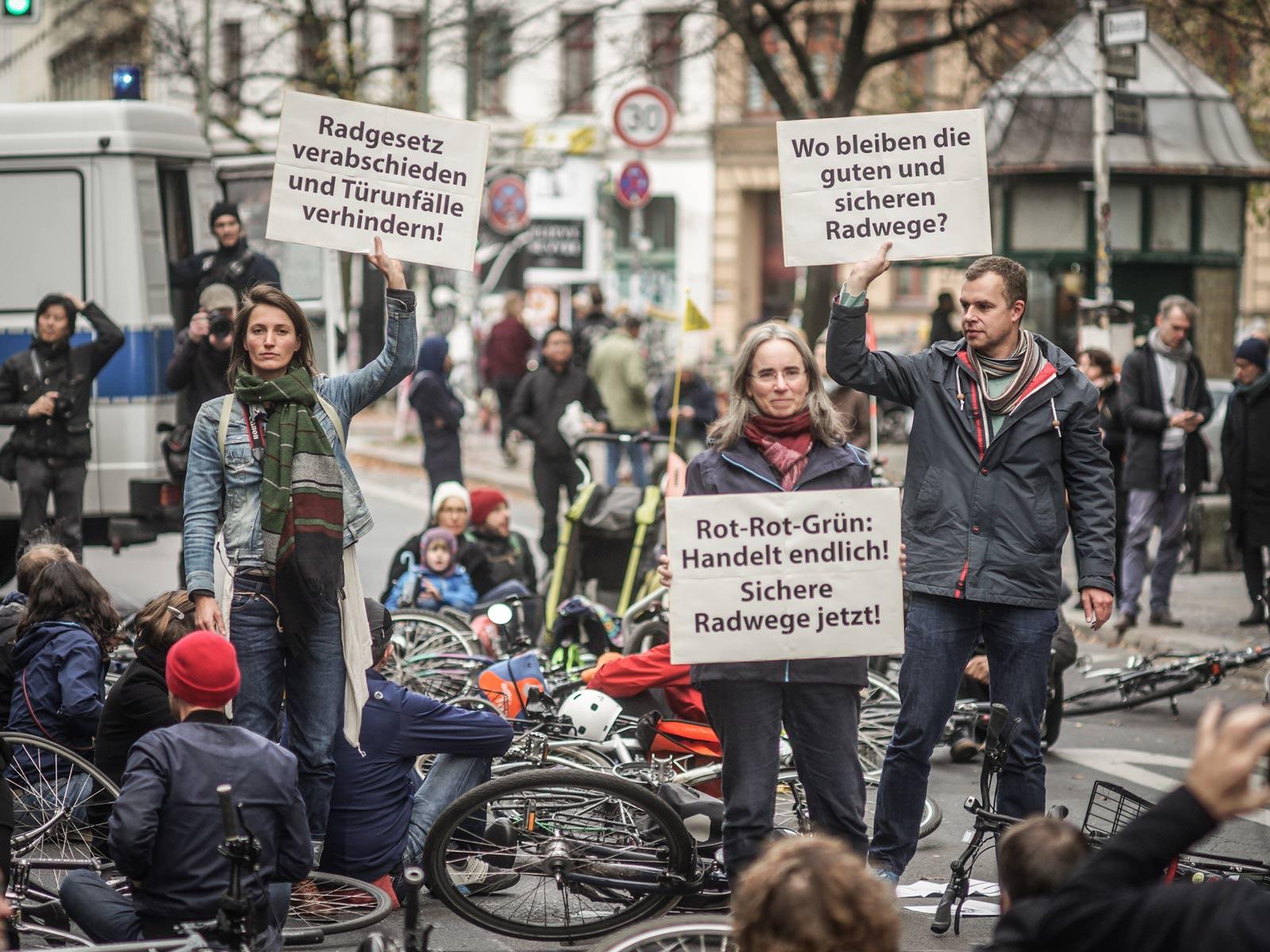 Eine Gruppe von Demonstranten hält Schilder für mehr Sicherheit für Radfahrer in die höhe.