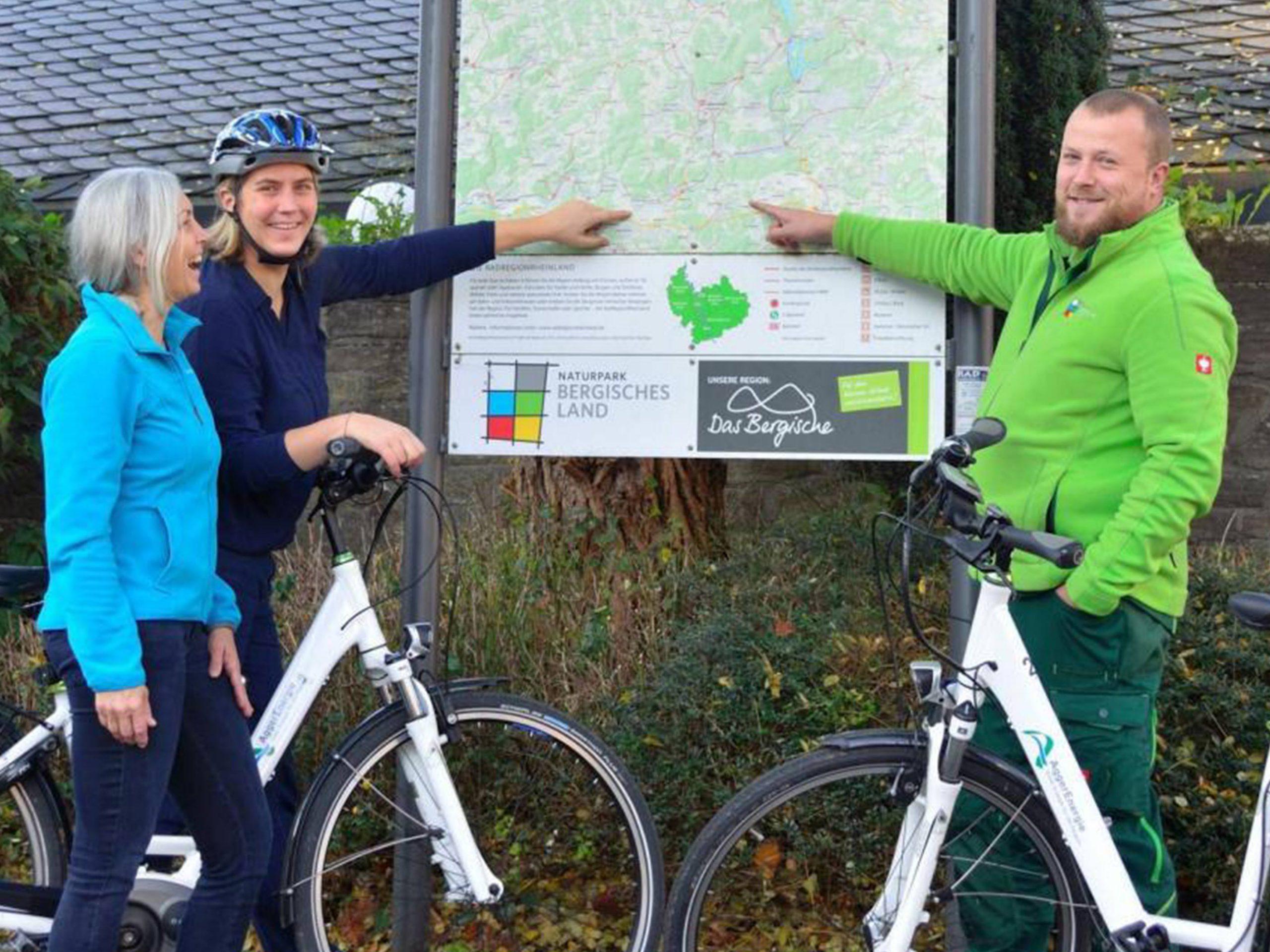Ein Mann und eine Frau mit Rädern zeigen auf eine Karte des Naturparks Bergisches Land.