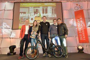 Vier Männer und eine Frau präsentieren ein kleines schwarzes e-Bike.