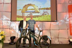 Zwei Männer präsentieren zusammen ein dunkelgraues e-Bike von Conway.
