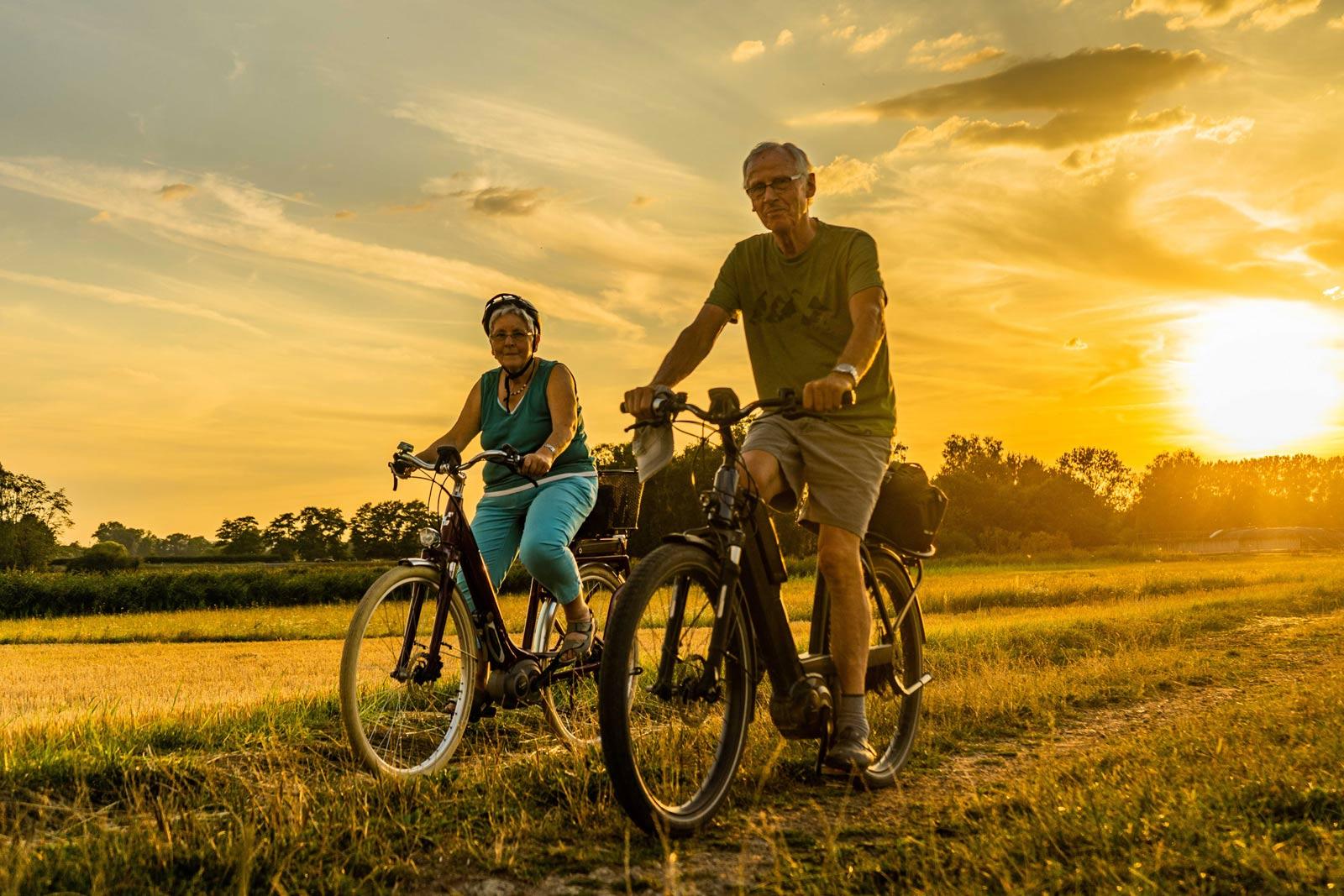 Ein älterer Mann und eine ältere Frau fahren mit dem Rad in der Abensonne über ein Feld.