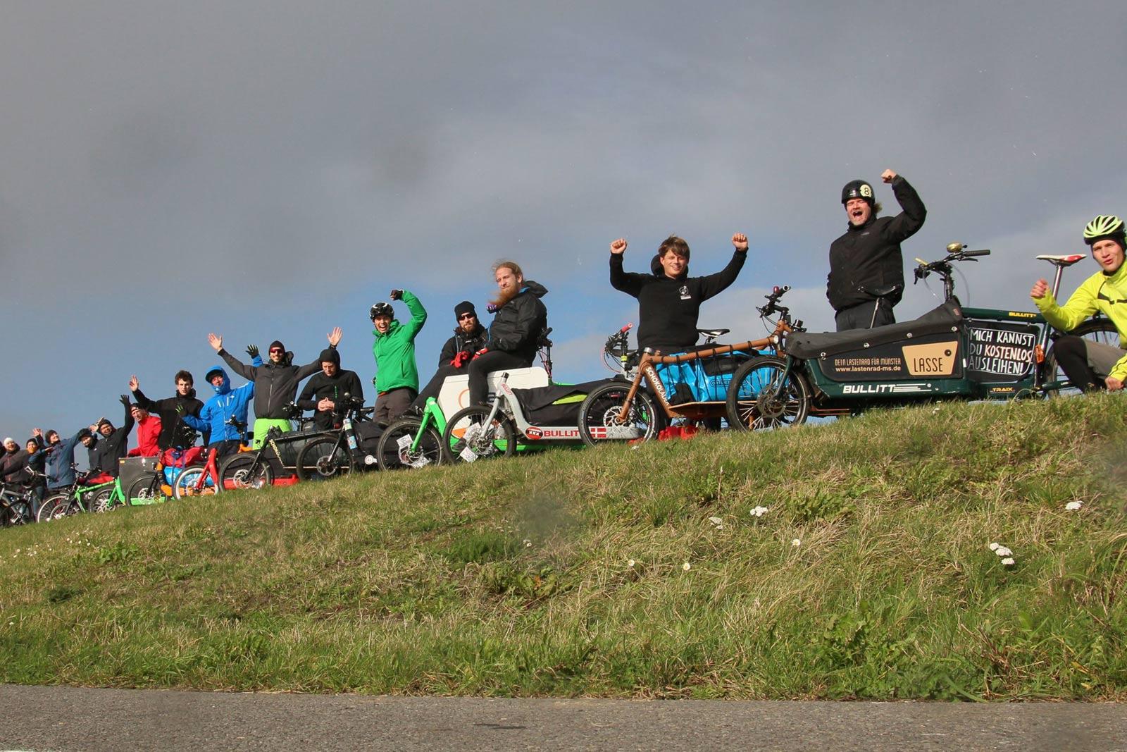 Eine Menschengruppe mit erhobenen Armen und Lastenrädern auf einem Grashügel.