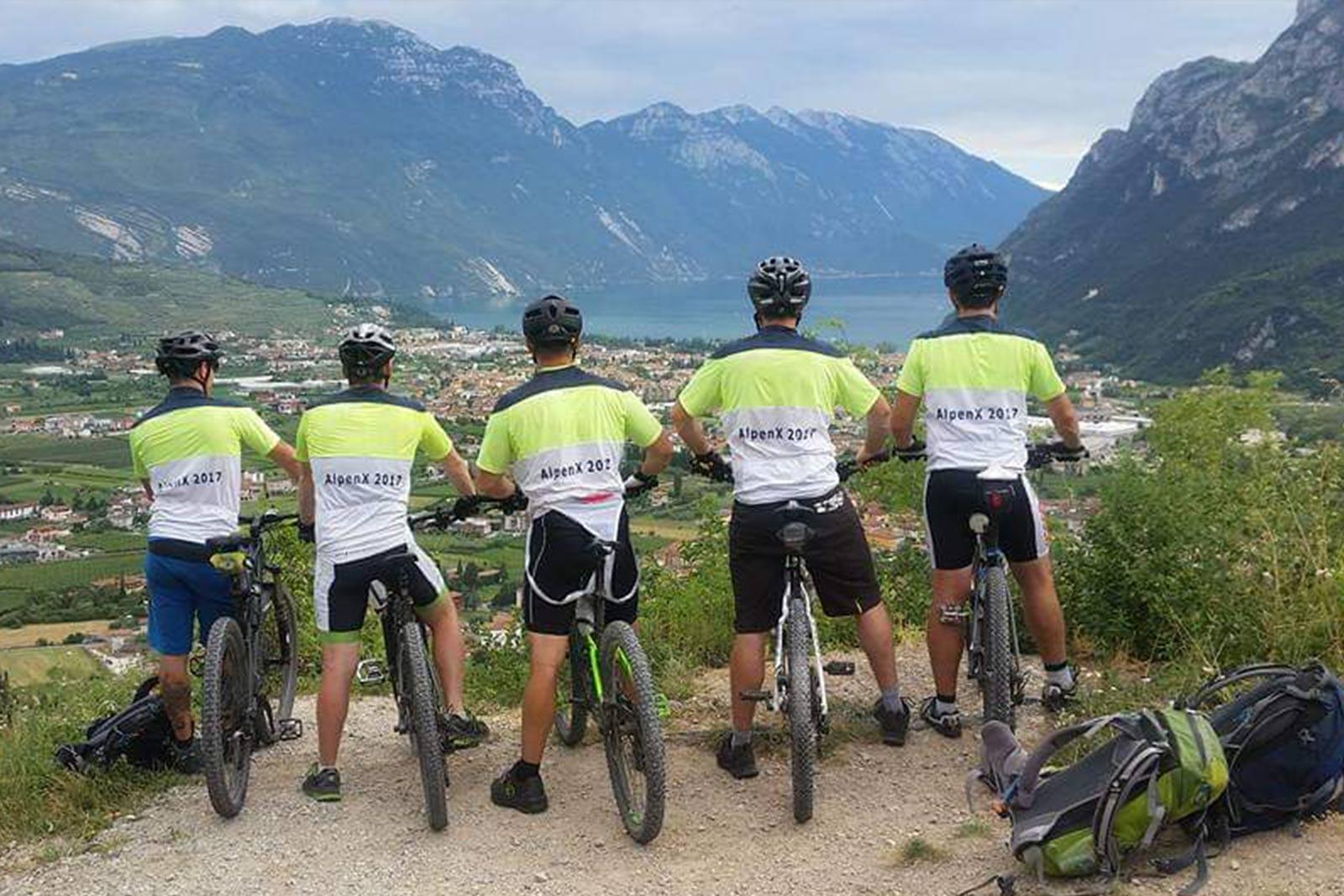 Fünf Männer auf Mountainbikes schauen auf ein Tal mit See und Bergpanorama.
