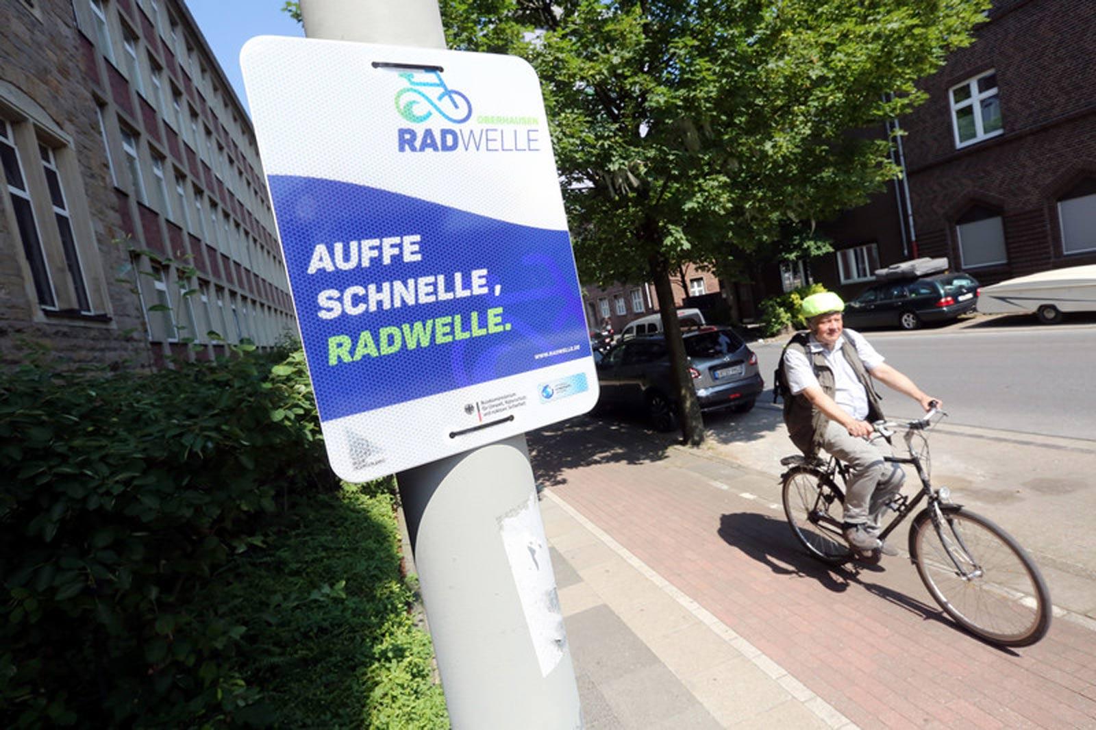 Im Vordergrund ein blau-weißes Schild der Radwelle und im Hintergrund ein Radfahrer.