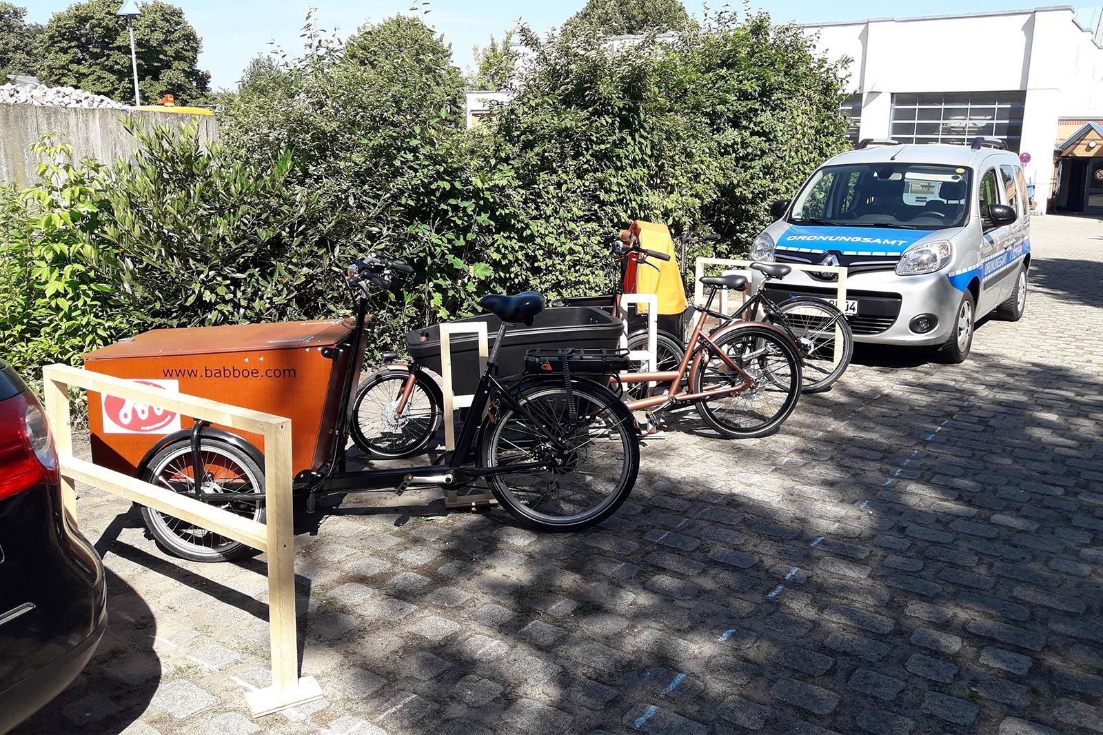 Drei ordnungsgemäß geparkte Lastenräder in einer Reihe vor einem Fahrzeug des Ordnungsamts.