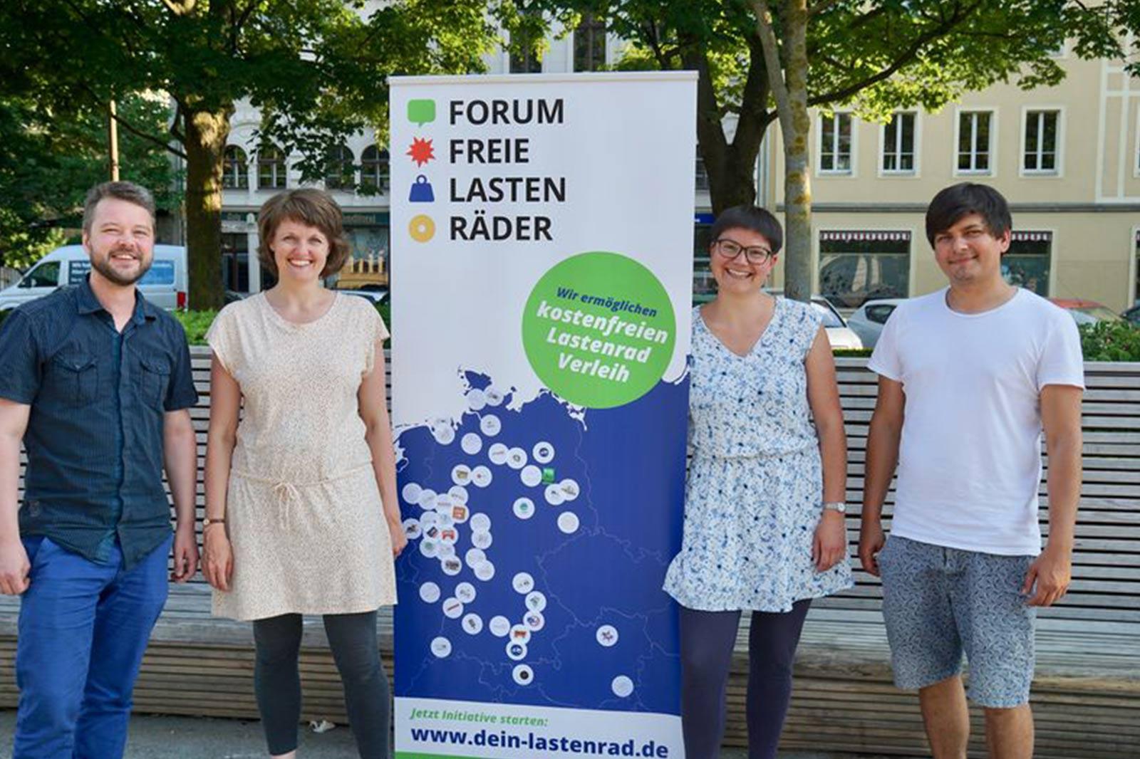 Je eine Frau und ein Mann rechts und links neben einem Banner des Forum Freie Lasten Räder.