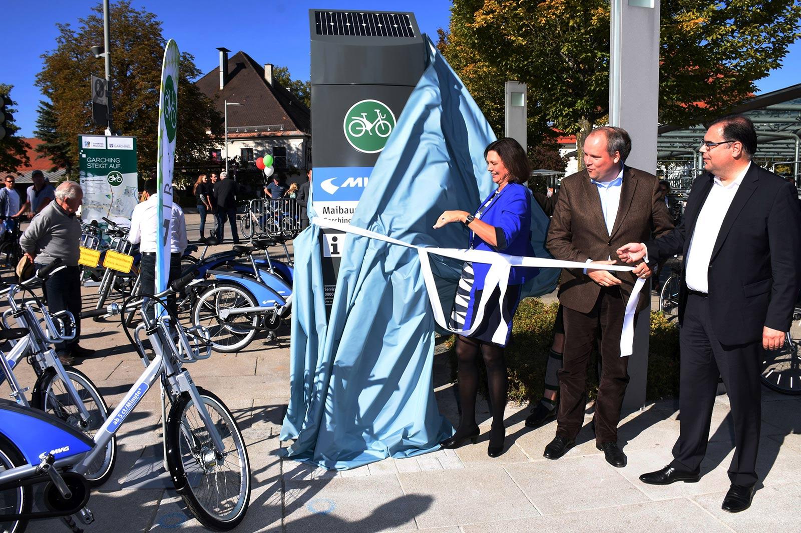 Zwei Männer und eine Frau enthüllen eine Station für Leihräder.