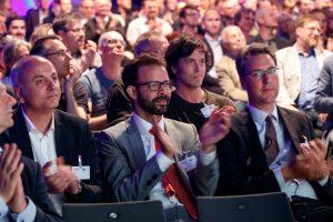 Beifall von drei Herren in Anzügen im Publikum für die Preisträger.