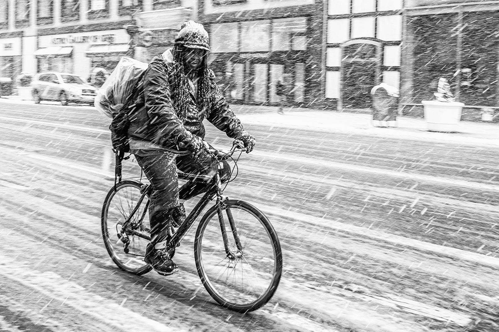 Schwarz-weiß Bild eines Mannes der im Schneetreiben Fahrrad fährt.