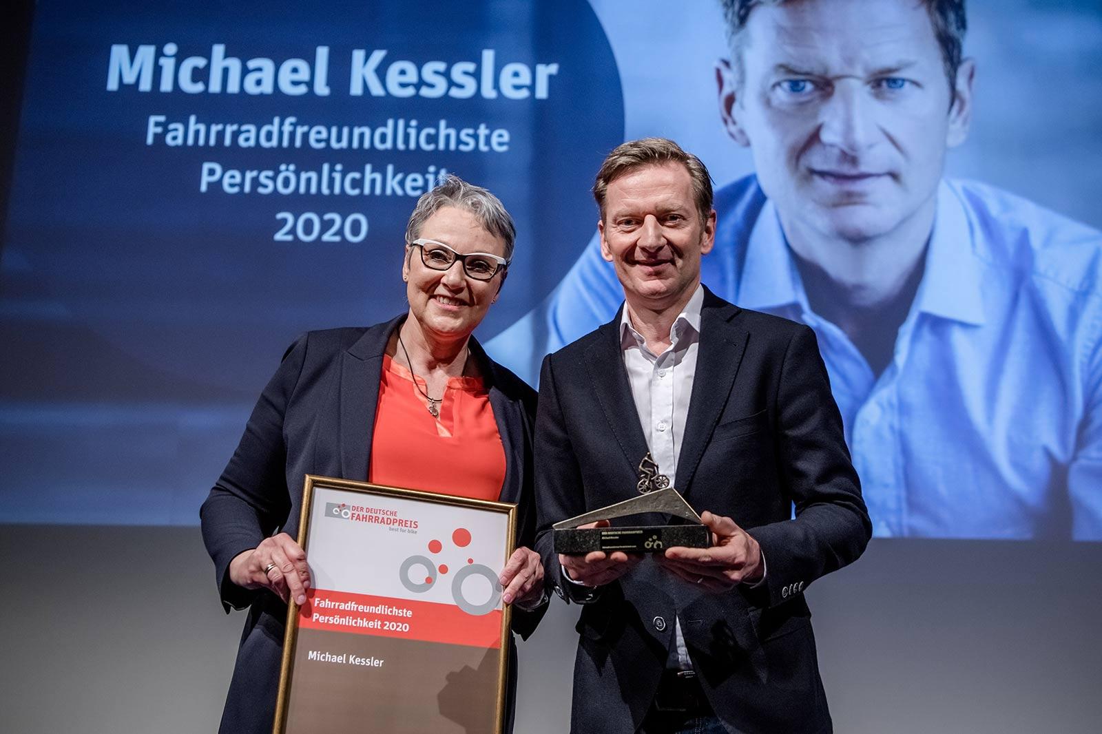 Christine Fuchs und Michael Kessler halten lächelnd Urkunde und Preis in die Kamera.