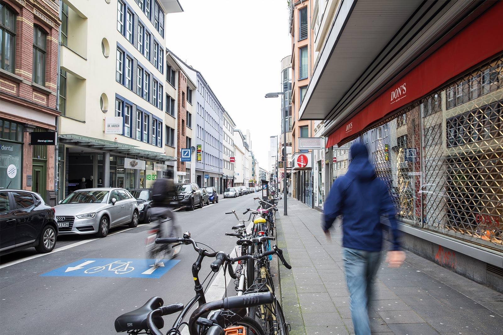 Eine Fahrradstraße im Stadtinneren. Rechts und links sind Gebäude und geparkte Autos und Räder.