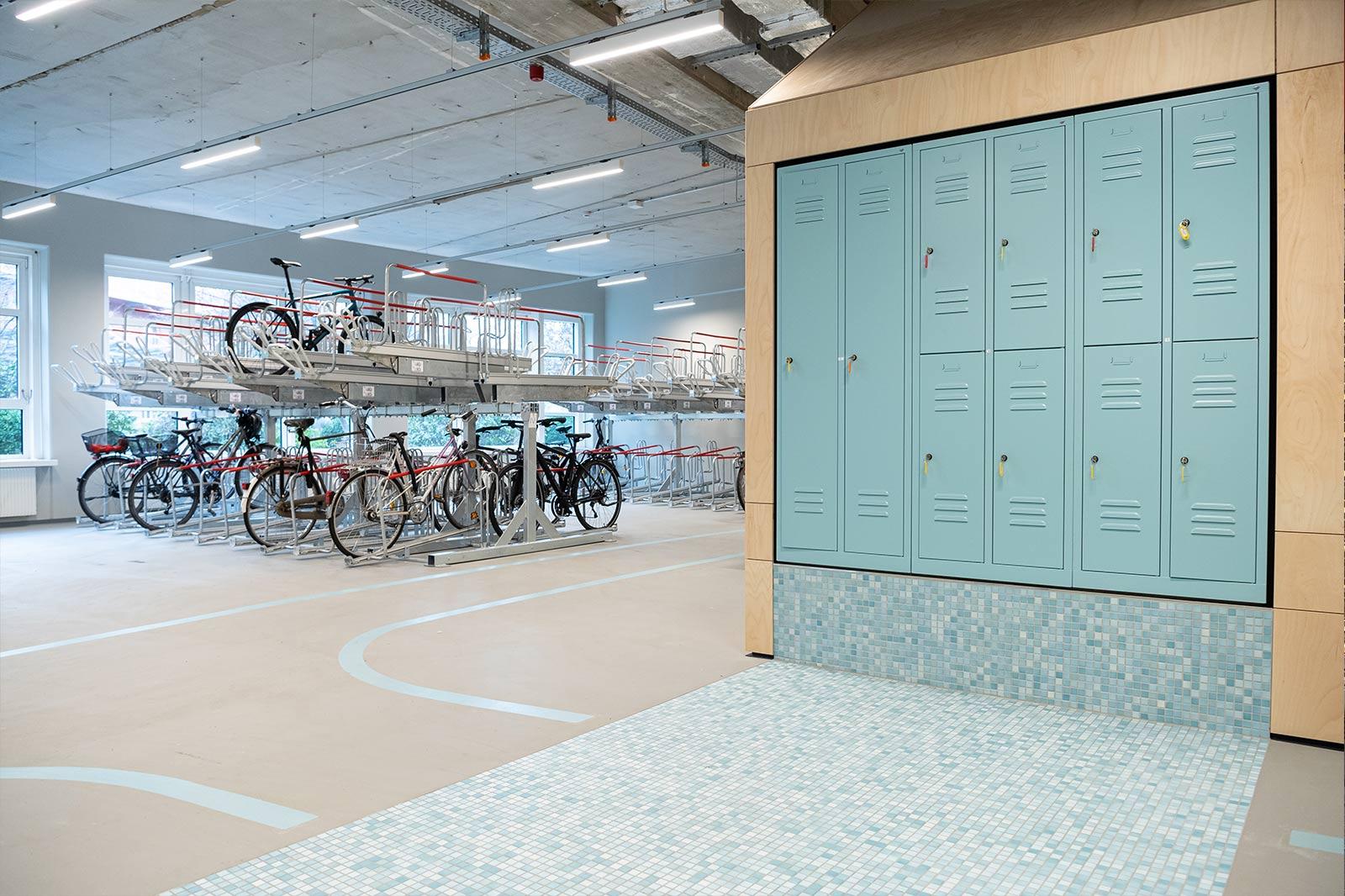 Fahrradparkhaus von innen mit Rädern auf zwei Etagen und blauen Spinden.