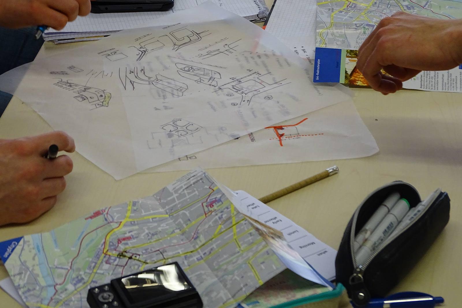 Nahaufnahme einer Schreibtischoberfläche auf der Pläne und Skizzen liegen.