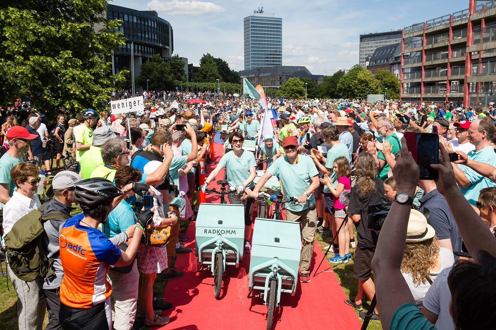 Zwei Personen in hellblauen T-Shirts schieben hellblaue Lastenräder durch eine Menschenmenge.