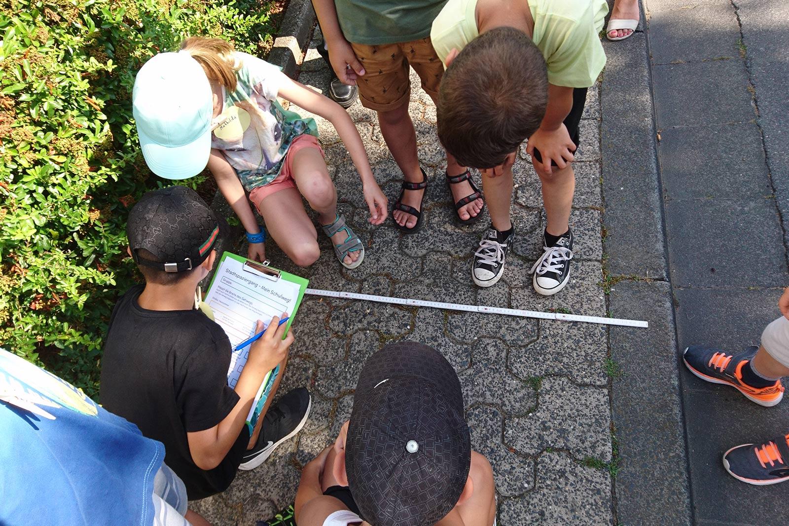 Kinder messen mit einem Zollstock die Gehwegbreite und notieren das Ergebnis auf einem Klemmbrett.