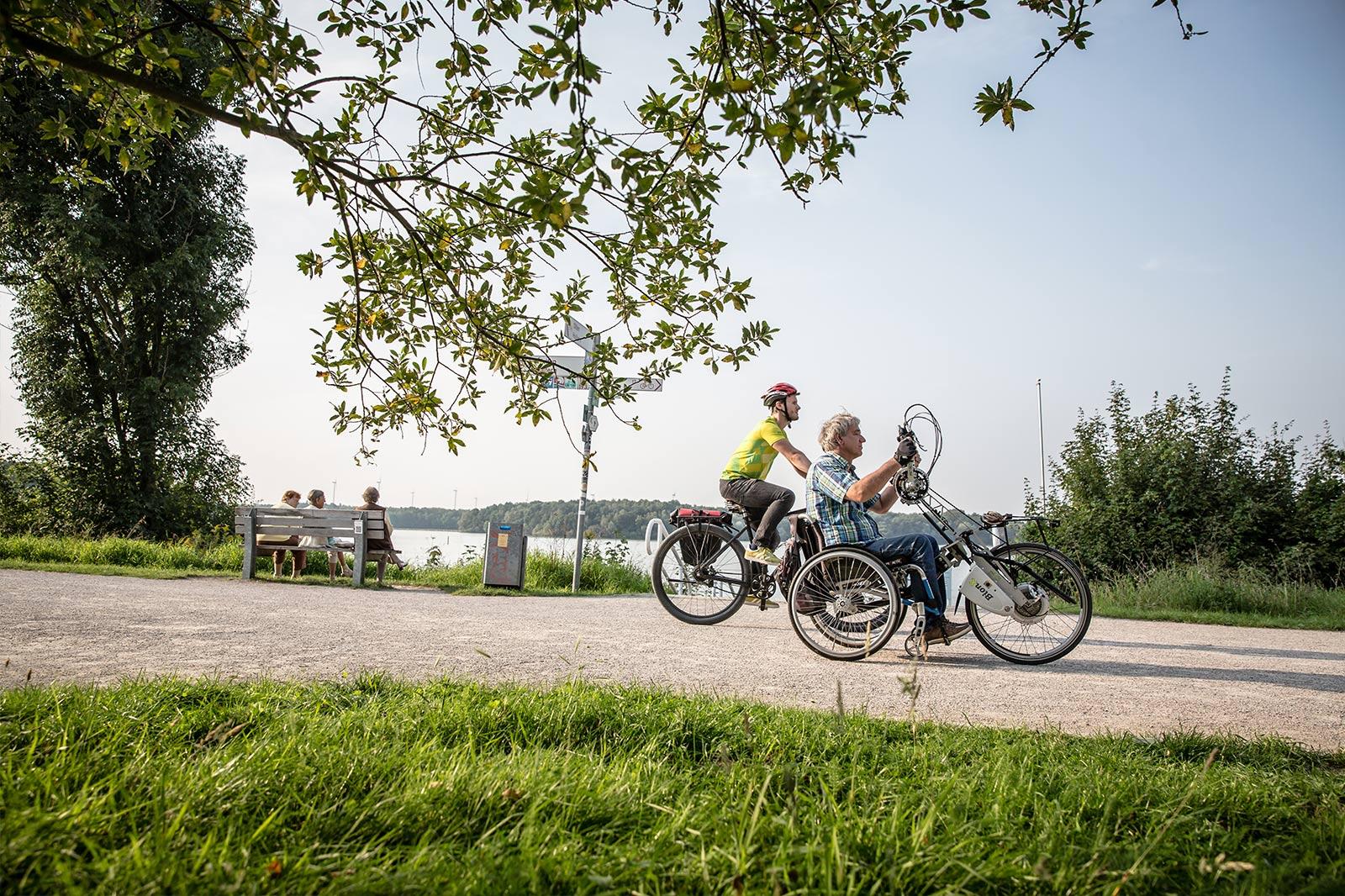 Mann auf einem Sitzrad und Mann auf einem Fahrrad auf einem Schotterweg entlang eines Flusses.