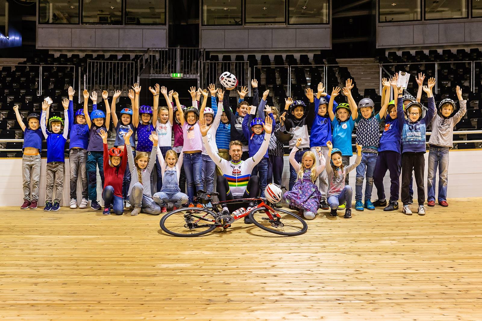 Eine Gruppe Kinder und ein Radprofi auf einer Radrennbahn. Alle heben die Hände in die Höhe.