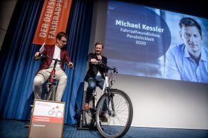 Michael Kessler und der Moderator unterhalten sich auf Fahrrädern sitzend.