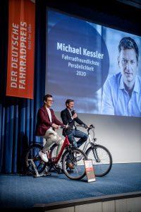 Michael Kessler und Harald Greising unterhalten sich auf Fahrrädern sitzend.