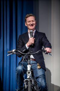 Frontalaufnahme von Michael Kessler auf einem Rad auf der Bühne mit Mikro in der Hand.