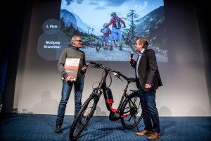 Zwei Männer mit Mikrofonen neben einem schwarz-roten Fahrrad auf der Bühne.