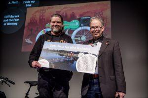 Zwei Männer halten einen Gutschein für eine Radreise in die Kamera.