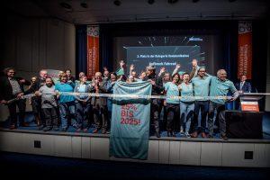 Eine große Gruppe steht auf der Bühne und hält ein hellblaues Banner mit Aufschrift hoch.