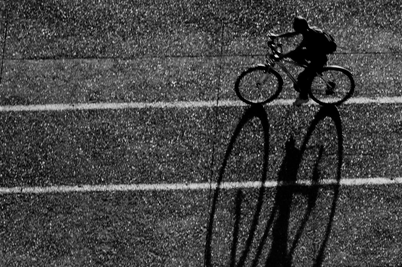 Schwarz-weiß Bild eines Fahrradfahrers mit sehr großem Schatten.