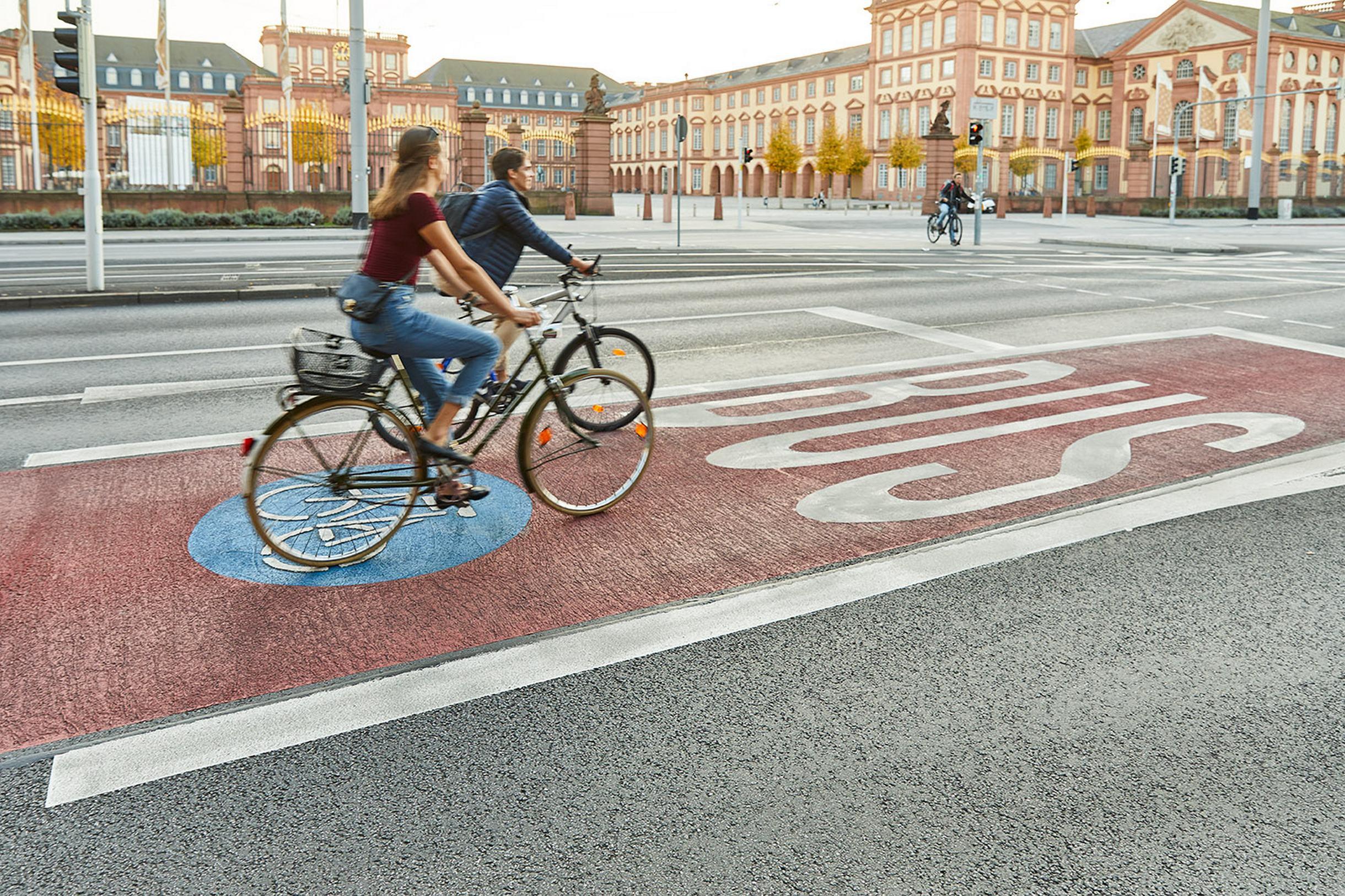 Zwei Fahrradfahrer auf der Radspur vor dem Schloss Mannheim.