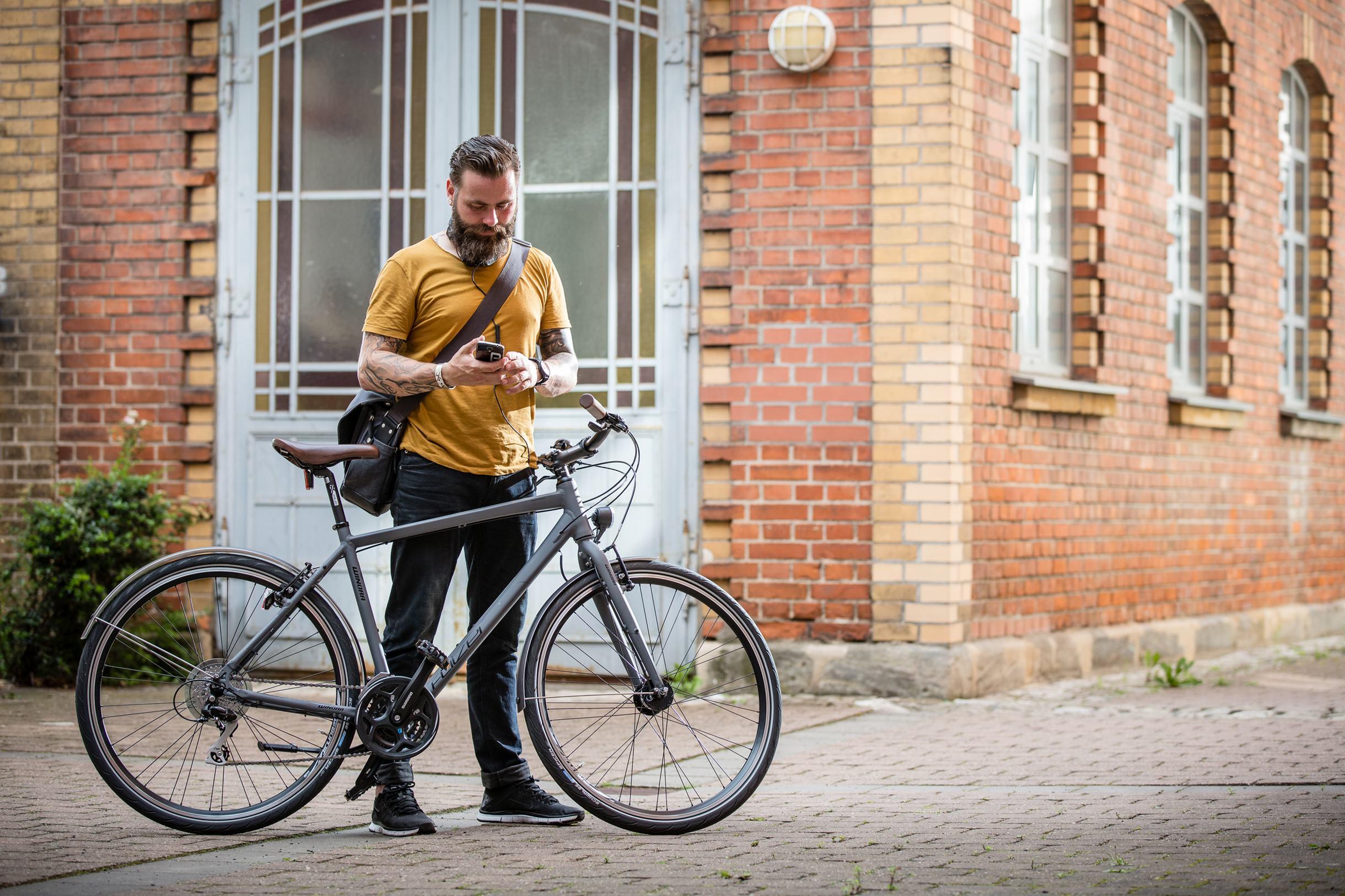 Mann mit grauem Fahrrad steht vor Backsteingebäude und schaut auf sein Handy.