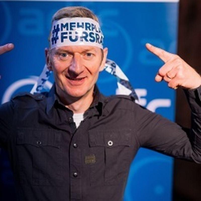 Michael Kessler mit einer weißen Banderole mit blauer Aufschrift um den Kopf.