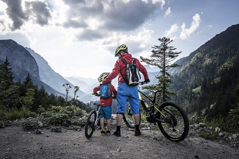 Ein Kind und ein Erwachsener mit Mountainbikes jeweils mit blauen Hosen