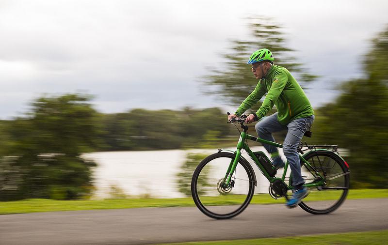 Mann mit grüner Jacke und grünem Helm fährt auf einem e-Bike an einem See.